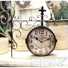 Metalowy zegar kolejowy ozdobiony metalową lilijką. zegar kolejowi, zegari dworcow, metalowi zegar, metalową lilijką, ozdobioni metalową, kolejowi ozdobioni
