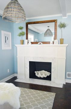 Completing our $197 fireplace makeover (marble herringbone tile, a framed out wooden mantel, and a whole lotta molding).