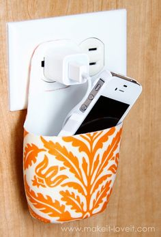 Take an old lotion bottle (this is a Johnson & Johnson baby shampoo bottle) and cut it to fit around an outlet and plug. Select some fabric and Mod Podge it on. Instant electronic device holder, clear counters..