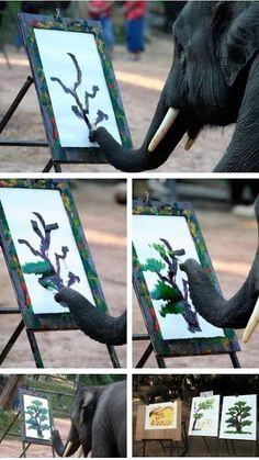 An elephant painting a tree