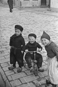 Children in Volendam costumes with wooden shoes and tricycle. Netherlands, 1937.