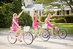 Bridesmaids in pink dresses, riding bikes down the road in an Oriental NC wedding by Cynthia Rose Photography