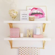 White shelves, gold brackets, and stylish knickknacks in place of a hanging mirror or pictures on a wall.