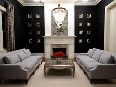 Not a fan of the black mirrored wall---but love the coffee table, chandalier, fireplace and sofas