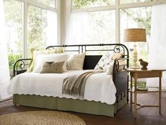 Crisp and Clean Daybed The wrought-iron daybed provides a place for guests to sleep without taking up too much space. Translucent draperies and crisp, clean bedding open up the space even more.