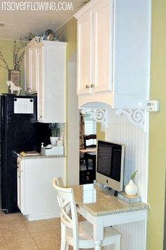Desk in kitchen - but I love the woodwork and scrolls underneath the top cabinet