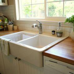 Farmhouse sink in butcher block countertop.