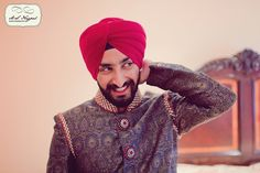 Sikh groom getting ready with red turban via IndianWeddingSite.com