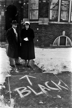 A couple who'd moved into an all-white neighbourhood looks at graffiti scrawled in front of their home. Chicago, 1957.   Francis Miller
