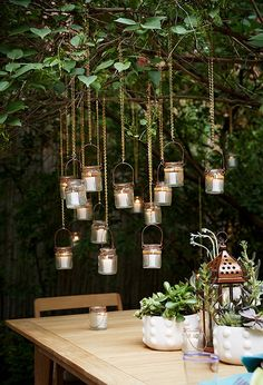 Using gold chains, Day hung up mini glass jar lanterns and staggered them from the branches so that they appear to almost float in midair.