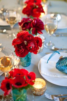 your blue mason jars w/red flowers. i like how they used all different kinds of red flowers... Pretty for a centerpiece on a dining room table