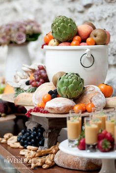 Savoury table featuring artisanal cheese and breads, grissini and fruits, charcuterie, sardines,   olives, and shot glasses filled with soup