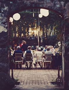An eclectic mix of paper lantern and vintage bulbs add to the beautiful landscape of their reception Maui wedding