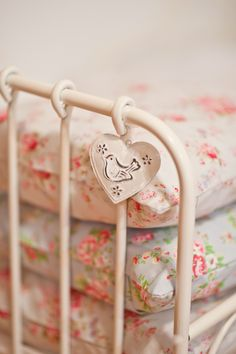 Tin bird charm on an iron bed.