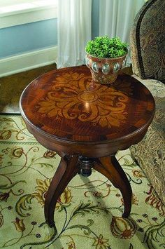 22in. Inlay Three Leg Adjustable Height Accent Table , Seven Seas, Hooker Furniture.    This traditional-styled accent table features a piano stool mechanism for height adjustment; simply turn the top to lower of raise the height. The top has an inlaid design with a scalloped apron and three lyre-shaped legs with carved detail. Birch Solids and Veneers; Metal.