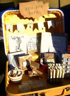 craft fair booth display using suitcases, maps, and paper goods