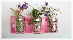 Flowers in mason jars mounted on a wall plaque--cabin shabby chic for a weekend cottage or in a rustic kitchen.