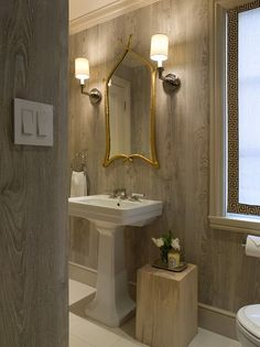 A wallpaper of white-washed wood is the perfect warm neutral to make the porcelain of the pedestal sink and gold framed mirror pop