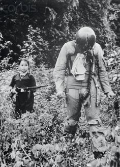 US Air Force First Lieutenant being held captive by a young North Vietnamese girl, Vietnam War, 1967