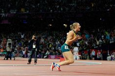 Australia's Sally Pearson falls to her knees after she was announced as the winner of the hurdles.