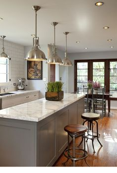 marble counters + white tile backsplash + stools + pendants