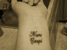 """Tattoo of the Latin phrase """"Nunc Coepi"""" which means """"Now I begin"""""""
