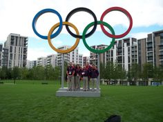 Gamesmakers team under Olympic Rings in main Village square. villag squar