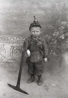 "Miner Boy: Children were cheap labor in the mines. This boy spent 10 hours a day in that outfit with only the light from that tallow wick lamp. He cleaned & played the part of a ""canary"" (kids were easier to replace than good miners). He was probably Finnish or Swedish & indentured to the company for the purpose of paying his fathers debts. The unions fought bloody battles to get these children out of the coal mines. This little guy worked (& likely died) in Utah or Colorado mines / Scott Cooper"