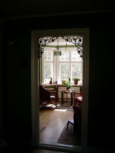 My Swedish house: view thru arch of bay window  Archway connecting the two reception rooms in my Swedish house (in Mullhyttan, Närke) with ornate, Victorian, cast iron brackets (painted gilt). The etched glass lampshade has a green glass bead fringe - very 1920s! by Anna Borsey