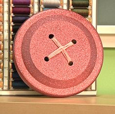 ButtonArtMuseum.com - How to make Big Buttons with Mark Montano  > using Frisbees, yarn, spray-paint & a drill ...how easy!  Have also seen this done with paper plates if someone doesn't happen to have a drill to go through the plastic Frisbees.   Cute idea for sewing or crafts room.