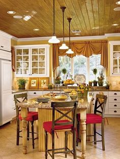 I adore the golden brown hue of the wooden ceiling in this posh, well sized country chic kitchen. #home #decor #country #chic #wood #yellow #red #lighting #ceiling