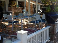 Outdoor living room porch with rug, pillows, fireplace and a blue & white table. Front-Porch-Ideas-and-More.com #porch blue tableset, patio, wrought iron, porch, iron rail