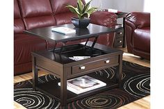 """The Hatsuko Lift-top Coffee Table from Ashley Furniture HomeStore (AFHS.com). The stylish contemporary design of the """"Hatsuko"""" accent table collection features a dark rich finish flowing along with ample lower shelf and table top storage space and stylish brushed nickel color hardware adorning the working drawers to create the perfect accent for any living area."""