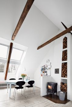 Love this log burner and storage for wood. Also love the high ceilings, white walls and wooden beams.