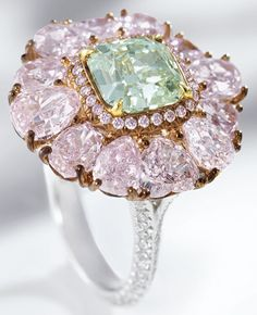 Rare Fancy Green Diamond, Pink Diamond and Diamond Ring - Centring on a cut-cornered square modified brilliant-cut fancy green diamond weighing 2.00 carats, surrounded by variously-shaped pink diamonds, the shoulders set with circular-cut diamonds, the pink diamonds and diamonds together weighing approximately 6.25 carats, mounted in 18 karat white and pink gold. Ring size: 6¼.