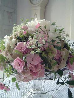 Create a flower arrangement on a cake stand.