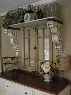 Salvaged corbels are used as shelf supports for a display shelf in the dining room. This is such a great look, especially with the salvaged windows.