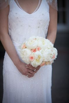 Fluffy white peonies with pops of pale pink roses.