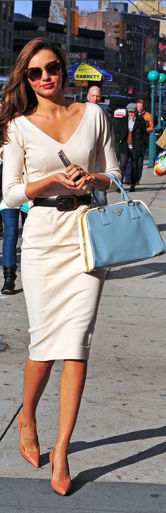 Miranda Kerr in an ivory sheath dress cinched with a black belt, with neutral heels, a blue and white handbag, and sunglasses.