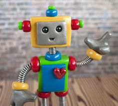 Wise and powerful humans, I shall create for you a wee colorful little robot with a child like nature who's only desire in life is to stand upon cake! This robot, both welcoming to male and female child will hold up 1 to 4 fingers proclaiming the age of your beloved child! Handmade by HerArtSheLoves of TheAwesomeRobots.com, $40.00