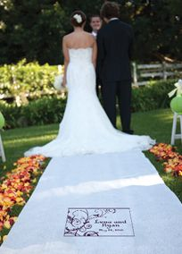 """Proudly display your names and wedding date to the world with this beautiful personalized fabric aisle runner. Aisle runner is a white on white printed victorian scroll that is semi-sheer and is available only in pattern shown. Comes with a handy pull cord and instructions. Personalized area is approximately 16.5"""" x 10.75"""". Background design color and personalization complements exclusive David's Bridal colors. Monogram will display as shown with your names and wedding date. Please enter y..."""