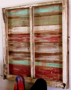old window frame with painted boards behind and hooks added