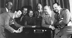 Group photograph of Eddie Anderson, Dennis Day, Phil Harris, Mary Livingstone, Jack Benny, Don Wilson, and Mel Blanc.