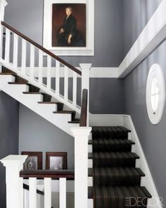 """""""Henri Le Menestrel of the French design resource Le Cèdre Rouge devised a neoclassical, New England–style home in the town of Saint-Cloud on the outskirts of Paris. Painted in Farrow & Ball's Down Pipe gray and decorated with a striped runner, the stairwell doubles as a witty portrait gallery of humans and canines."""""""