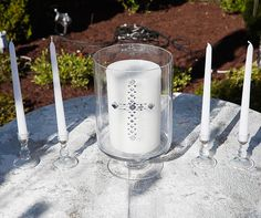 A crystal cross decorates a unity candle surrounded by tall white tapered candles.    Platinum At-Home Wedding, Silver and Purple, Glamorous, Elegant, Real Wedding || Colin Cowie Weddings