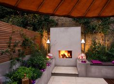 How about this for a fabulous evening relaxation or entertaining space! Love the restrained use of materials & colours - the purple accent colour in the plants being picked up in the accessories - a great outdoor living room.