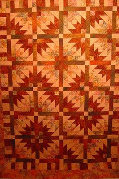 By Jessica's Quilting Studio.  Looks like a variation on Bonnie Hunter's Pineapple Blossom.  Love it!