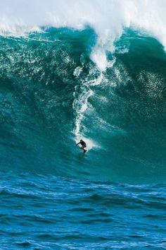 Surfer / riding a huge wave