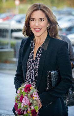 Radiant: The mother of four clutched a colourful bouquet at the event held at Tietgen business school