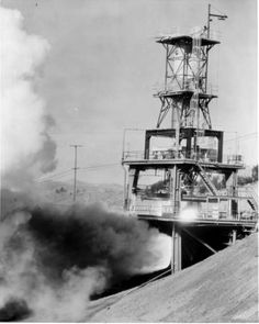 """Rocket test stand at Rocketdyne in Canoga Park, circa 1960. A related press release reads: """"The isolated laboratory, the most extensive rocket research center in the Free World, is located high in the Santa Susana Mountains 35 miles northwest of Los Angeles. Thousands of pounds of thrust are developed by rocket engines which will power guided missiles for the Air Force, Army and Navy."""" San Fernando Valley History Digital Library."""